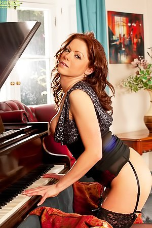 Miah Croft: Stockings-clad redhead spreading her thick legs on a grey sofa